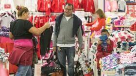 Shoppers, Manuel Orellano, middle, with his daughter Marcela, left, and her son Manuel, 6, shop for children clothing at JCPenney at Glendale Galleria shopping mall in Glendale, Calif, on Friday.